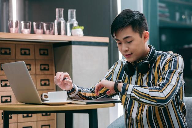 Молодой человек сидит с ноутбуком в кафе и внимательно смотрит на часы