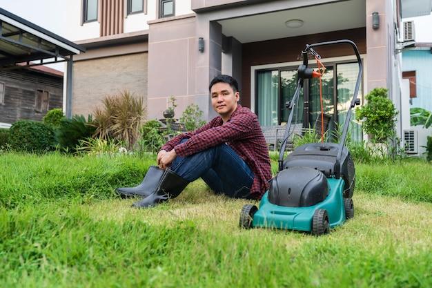 家で草刈りのために芝刈り機で座っている若い男