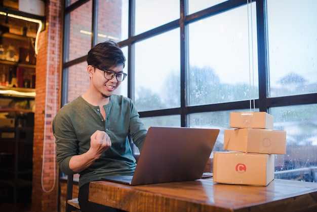 Young man sitting with computer and mobile phone on wooden floor with parcel selling ideas concept online.