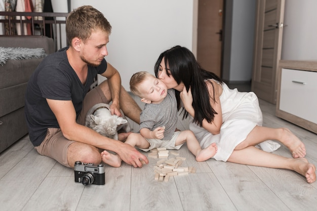 Young man sitting with dog looking at her wife kissing his son while playing with wooden blocks