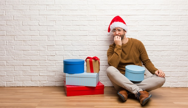 Young man sitting with gifts celebrating christmas biting nails, nervous and very anxious