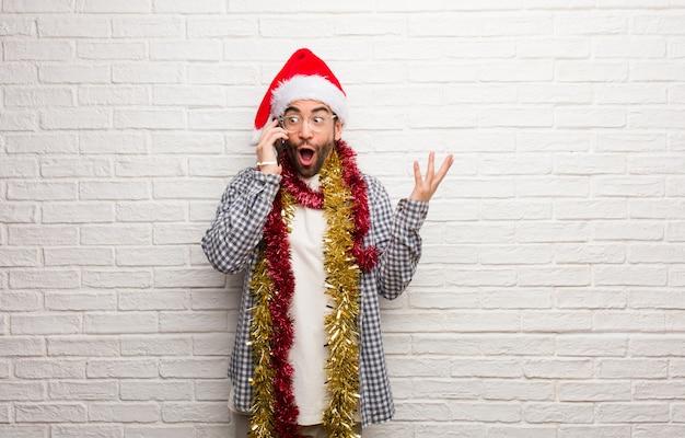 勝利や成功を祝うクリスマスを祝う贈り物と一緒に座っている若い男
