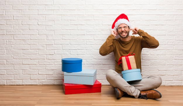 Young man sitting with gifts celebrating christmas covering ears with hands