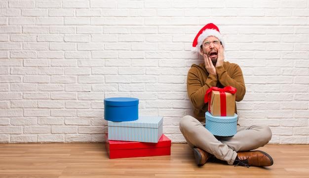 크리스마스 절망과 슬픈을 축하하는 선물로 앉아있는 젊은이