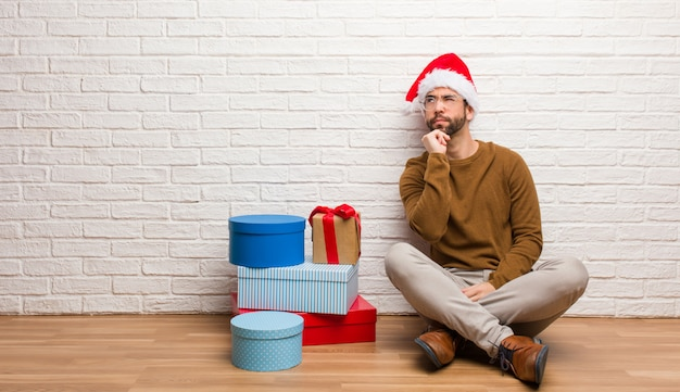 Young man sitting with gifts celebrating christmas doubting and confused