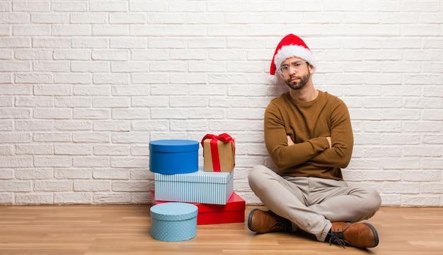 똑바로보고 크리스마스를 축 하하는 선물과 함께 앉아 젊은 남자