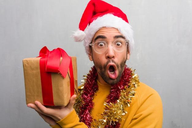サイドを指すクリスマスを祝う贈り物と一緒に座っている若い男