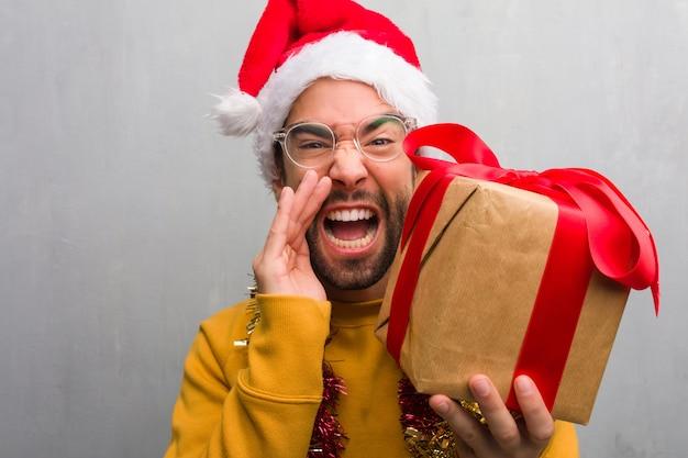 正面に何か幸せを叫ぶクリスマスを祝うプレゼントと一緒に座っている若い男