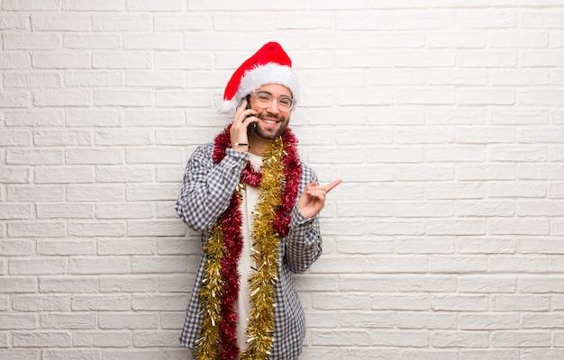 若い、笑顔と横を指しているクリスマスを祝うプレゼントと一緒に座っている男