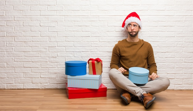 Young man sitting with gifts celebrating christmas thinking about an idea