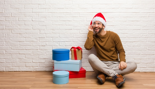 Young man sitting with gifts celebrating christmas try to listening a gossip