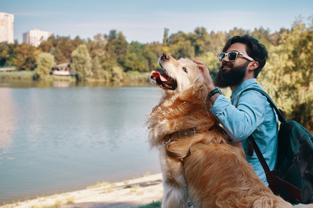 公園の椅子に彼の犬と一緒に座っている若い男