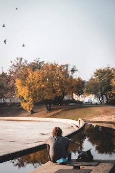 ハンガリーのブダペスト市の公園で彼の電話で座っている若い男