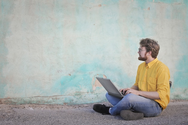 Young man sitting with a laptop next to an old wall