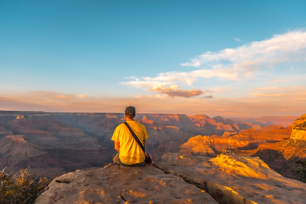 A young man sitting with yellow shirt at sunset at the powell point of grand canyon. arizona, vertical photo