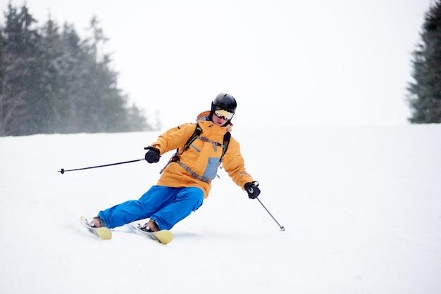 Лыжник молодого человека в лыжной спортивной одежде делает умелые маневры на лыжах. катание на лыжах и поворот на заснеженный горный спуск