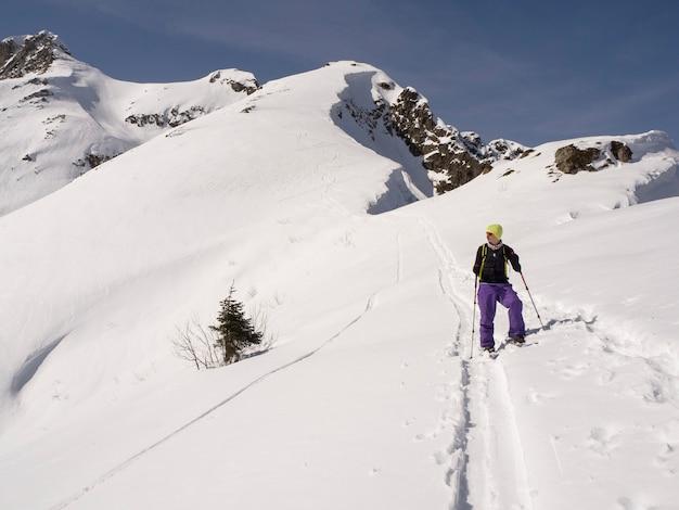 산 피크 배경에서 스키 젊은 남자