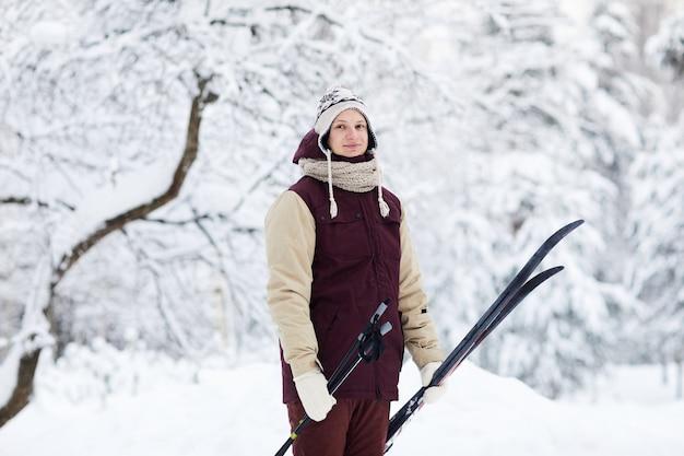 Молодой человек на лыжах в лесу