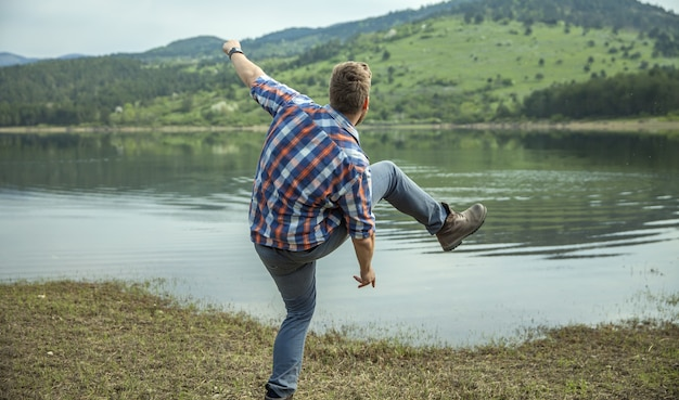 湖の水で石をスキップする若い男
