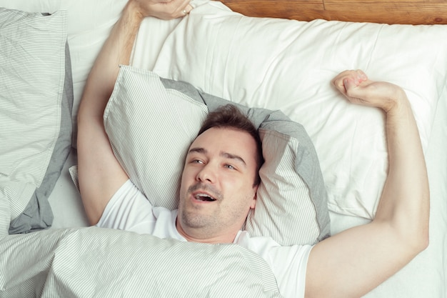 Young man sleeping on bed in bedroom