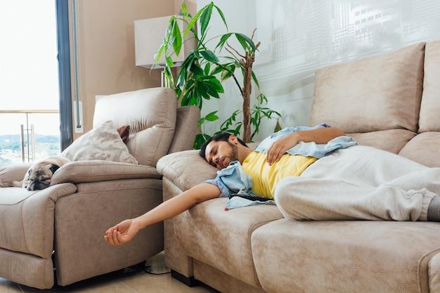 Молодой человек спит на диване