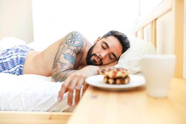 朝のベッドで寝る若い男