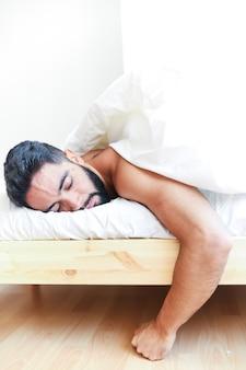 Молодой человек спит на кровати
