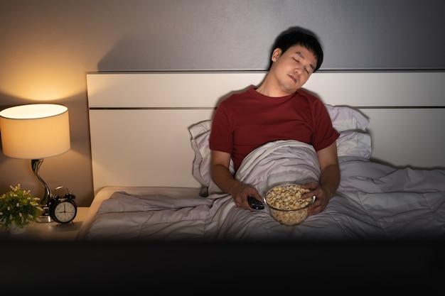 Молодой человек спит во время просмотра телевизора на кровати ночью