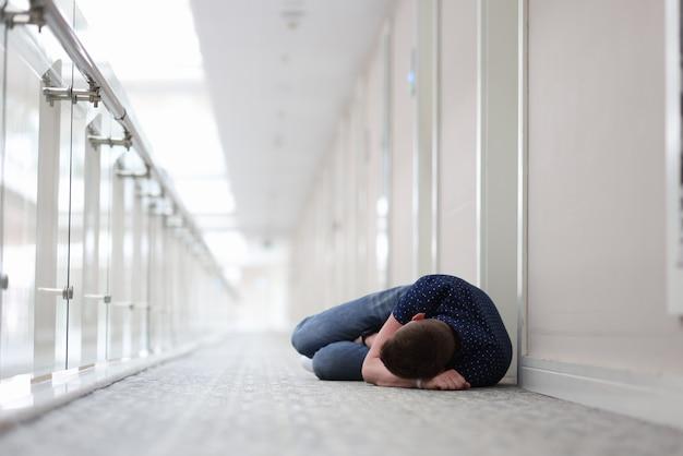Молодой человек спит под дверью гостиничного комплекса