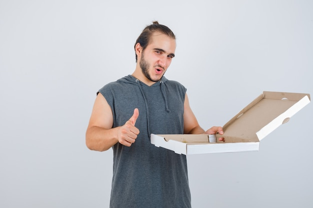 Young man in sleeveless hoodie holding opened pizza box while showing thumb up and looking delighted , front view.