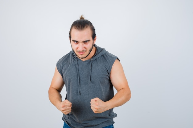 Young man in sleeveless hoodie standing in fight pose and looking spiteful , front view.