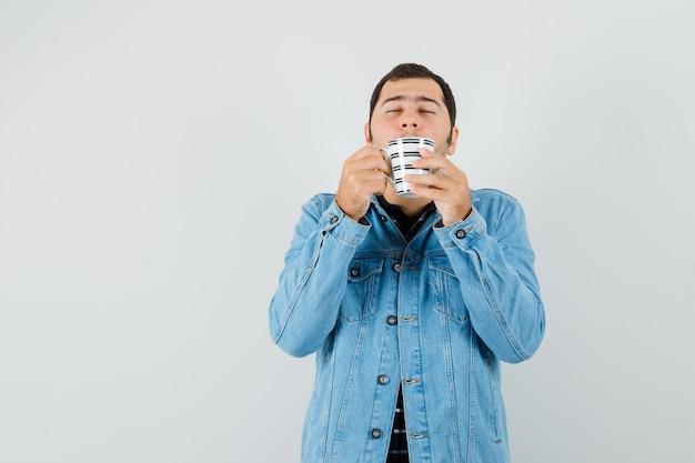 Молодой человек нюхает кофе в футболке, куртке и выглядит довольным, вид спереди.