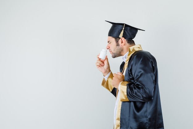 Giovane uomo odorando pillole in bottiglia in uniforme laureato e guardando disgustato.