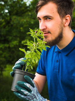 Young man smelling the potted plant