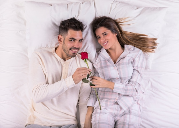 Young man smelling rose in bed with woman