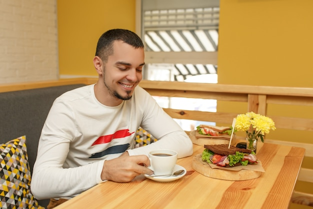 Young man smiles and take cup with coffee, breakfast in cafe