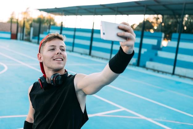 遊び場で携帯電話を取りながら若い男が微笑む