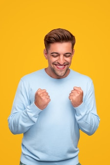 Молодой человек улыбается и празднует успех