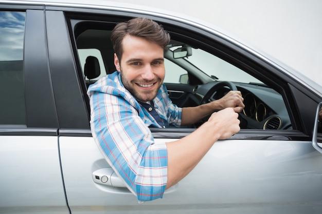 若い男は、彼の車で笑顔と運転