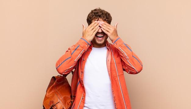 Молодой человек улыбается и чувствует себя счастливым, закрывает глаза обеими руками и ждет невероятного сюрприза. студенческая концепция
