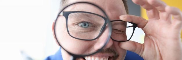 彼の目の前に拡大鏡を笑顔で保持している若い男クローズアップエラーの概念