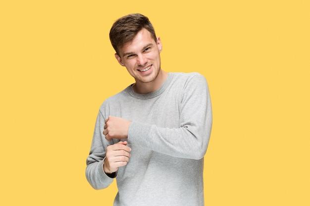 웃 고 노란색 스튜디오 배경에 카메라를보고 젊은 남자