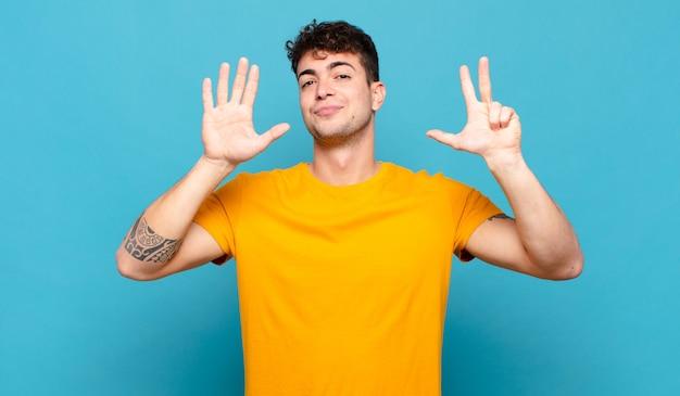 若い男は笑顔でフレンドリーに見え、手を前に向けて8番または8番を示し、カウントダウン