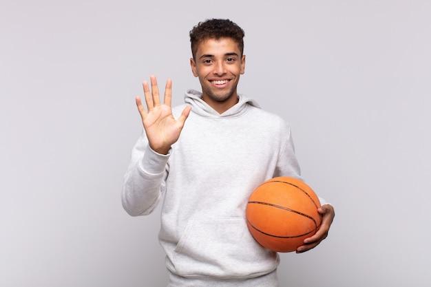 젊은 남자 웃 고 친절 하 게 찾고, 앞으로 손으로 숫자 5 또는 5를 보여주는 카운트 다운. 바구니 개념
