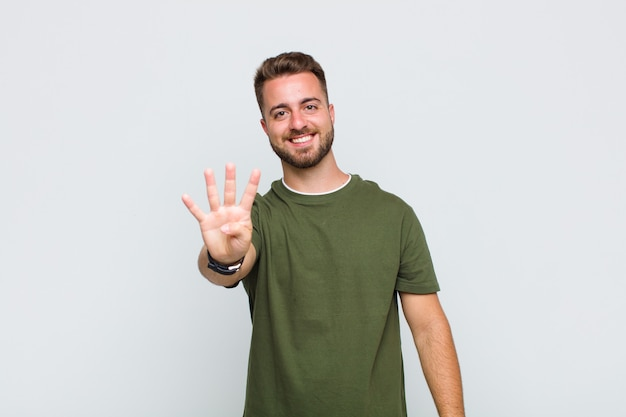 Молодой человек улыбается и выглядит дружелюбно, показывает номер четыре или четвертый с рукой вперед, отсчитывая