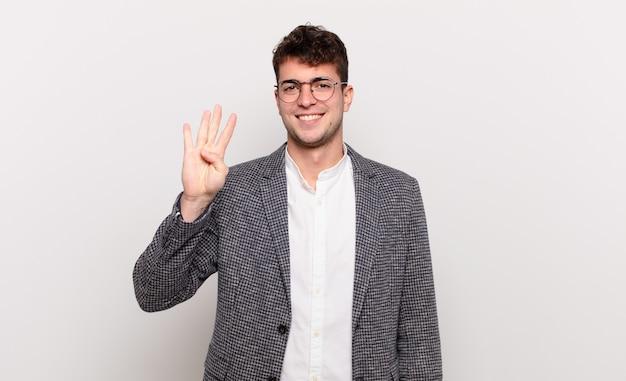 Молодой человек улыбается и выглядит дружелюбно, показывает номер четыре или четвертый с рукой вперед, считает