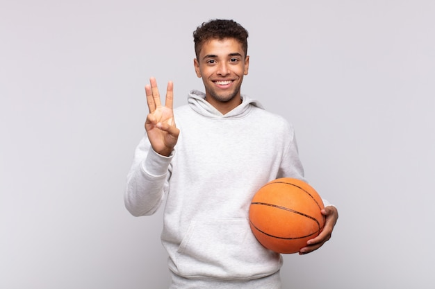 若い男は笑顔でフレンドリーに見え、手を前に向けて3番目または3番目を示し、カウントダウンします。バスケットコンセプト