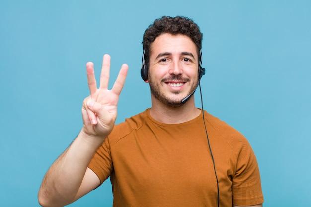 若い男は笑顔でフレンドリーに見え、前に手を前に3または3番目を示し、カウントダウン