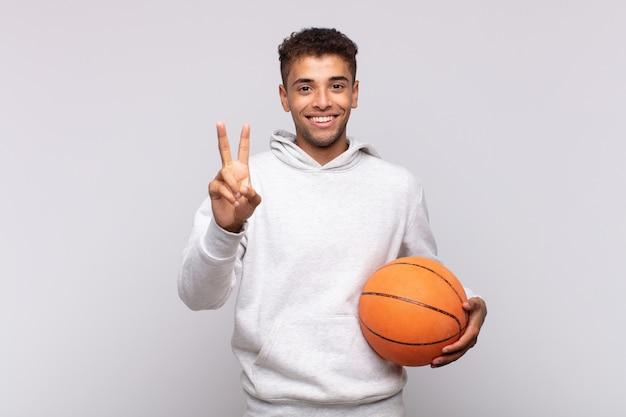 若い男は笑顔でフレンドリーに見え、手を前に向けて2番目または2番目を示し、カウントダウンします。バスケットコンセプト