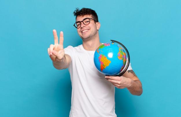 젊은 남자가 웃고 행복하고 평온하고 긍정적 인 찾고 한 손으로 승리 또는 평화를 몸짓으로합니다.